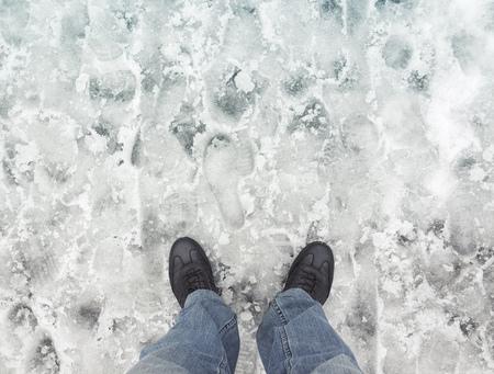 pieds sales: pieds m�les dans les nouvelles chaussures en cuir debout sur route enneig�e humide sale, vue � la premi�re personne Banque d'images