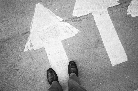 roadside stand: Male feet in new black shining leather shoes stand on asphalt pavement with white arrows pedestrian crossing road marking, first person view Stock Photo