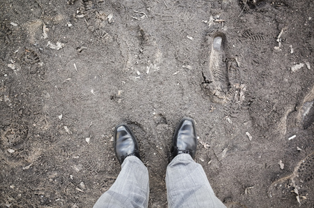 dirty feet: Male feet in new black shining leather shoes stand on dirty rural road, first person view Stock Photo