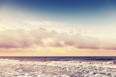 tonal: Dramatic morning seascape, colorful cloudy sky over horizon on the beach. Vintage tonal correction filter
