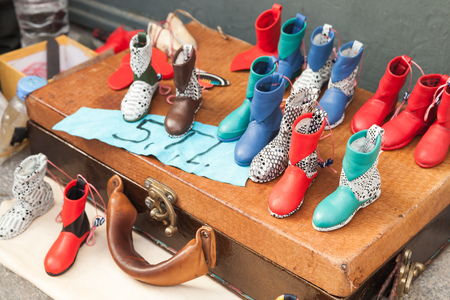 genuine leather: Izmir, Turkey - February 5, 2015: Traditional Turkish handmade souvenirs, colorful boots made of genuine leather stand on old bag