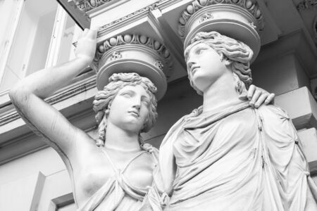caryatids: Caryatid. Statues of two young women in form elegant columns supporting a portico, Josefsplatz, Vienna. Black and white photo Stock Photo