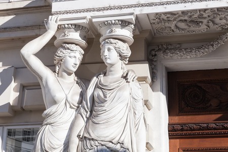portico: Caryatid. Statues of two young women in form elegant columns supporting a portico, Josefsplatz, Vienna