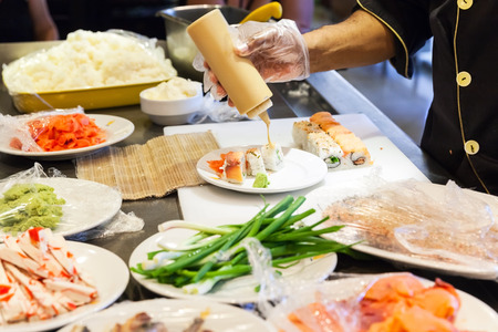 adds: Preparing of traditional Japanese sushi rolls with salmon, cook adds sauce on plate. Selective focus