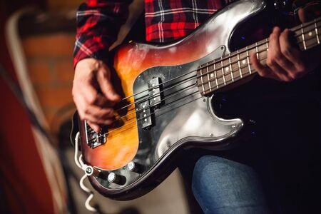 bass guitar: Rock music background, bass guitar player, closeup photo with selective focus and motion blur effect