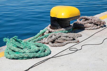 mooring bollard: Yellow mooring bollard and nautical ropes are on pier in cargo port