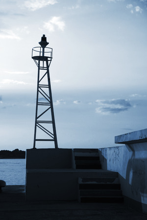 leading light: Truss design lighthouse tower in port of Nesebar, Bulgaria. Blue toned, dark silhouette photo Stock Photo