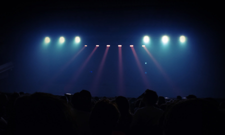 spectators: Abstract entertainment event background. Blurred photo with spotlights scene illumination. Spectators watch the stage