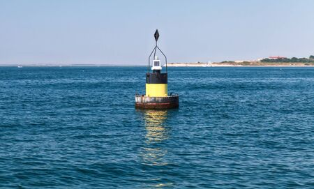 navigate: Black modern navigation buoy with yellow stripe floating on a sea water. East Cardinal Mark helps ships to navigate safely. Black Sea, Bulgarian coast