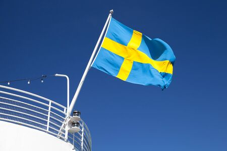 the swedish flag: Swedish flag mounted on the stern of white passenger ship waving over blue sky background