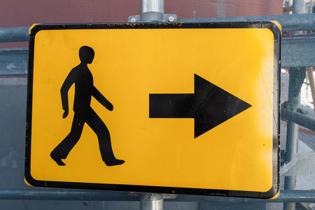 bypass: Pedestrians bypass direction. Yellow road sign on construction site border