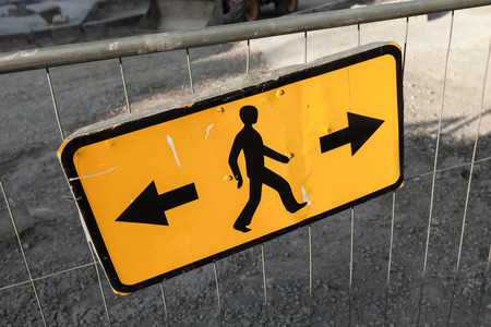 no way out: Pedestrians bypass directions. Yellow road sign on construction site border Stock Photo