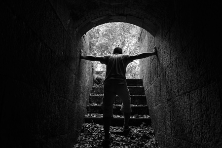 catacomb: Tired man goes out of dark stone tunnel with glowing end, monochrome photo Stock Photo