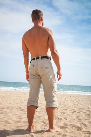the stands: Barefoot sporty man stands on sandy summer beach and looks at the sea