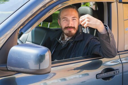 urbanite: Smiling Asian man with keys as a driver of modern Japanese suv, outdoor portrait in open car window Stock Photo