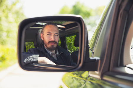 urbanite: Serious Asian man as a driver looks in car mirror, outdoor summer portrait Stock Photo