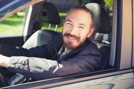 urbanite: Smiling Asian man as a driver of modern Japanese suv, outdoor portrait in open car window, vintage stylized photo with tonal correction photo filter