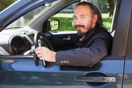 urbanite: Bearded Asian man with keys as a driver of modern Japanese suv, outdoor portrait in open car window