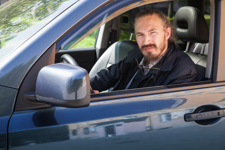 urbanite: Bearded serious Asian man with keys as a driver of modern Japanese suv, outdoor portrait in open car window