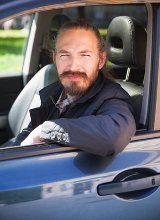 urbanite: Positive Asian man as a driver of modern Japanese suv, vertical portrait in open car window Stock Photo