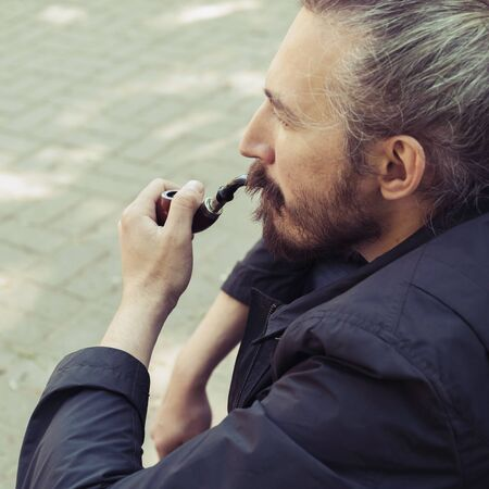 hombre con barba: Bearded man smoking pipe, square outdoor portrait with selective focus and vintage tonal correction photo filter, old style effect Foto de archivo
