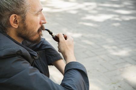 hombre con barba: pipa de fumar hombre de la barba, retrato al aire libre con el enfoque selectivo