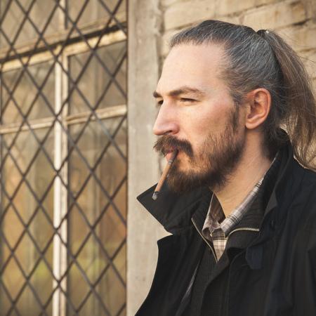 hombre fumando puro: Hombre con barba del cigarro fumar, retrato cuadrado al aire libre con el enfoque selectivo Foto de archivo