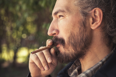 hombre fumando puro: Bearded Asian man smoking cigar, outdoor profile portrait with selective focus