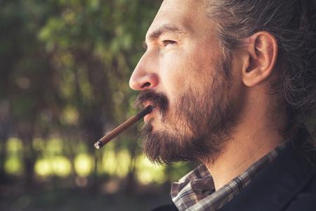 hombre fumando puro: Barbudo asiática de fumar cigarros hombre, retrato de perfil al aire libre con el enfoque selectivo y cálido efecto de filtro de corrección tonal Foto de archivo