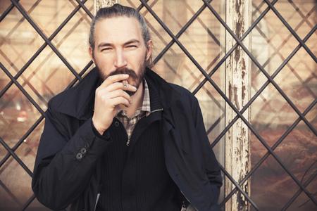 hombre con barba: Hombre barbudo fumar cigarrillos, retrato al aire libre con el enfoque selectivo