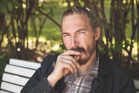 hombre fumando puro: Barbudo de fumar cigarros hombre en parque del verano, retrato al aire libre con el enfoque selectivo Foto de archivo