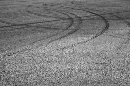 Abstract transportation background with dark tire tracks on gray asphalt road