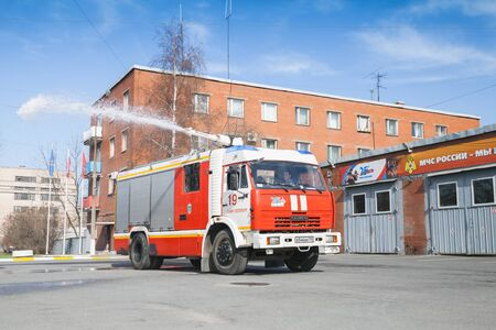 voiture de pompiers: St-Petersburg, Russia - April 9, 2016: Kamaz truck 43253 as a Russian fire engine modification with running water hose