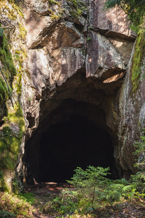 cave exploring: Entrance to dark cave in the rock, vertical photo