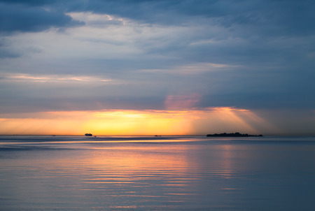 still water: Sunset over Baltic Sea. Cloudy sky, still water and ships in the distance Stock Photo