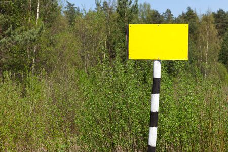white pole: Empty yellow sign board on striped black and white pole over summer nature background
