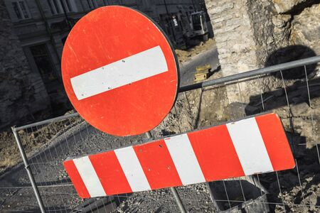 no entry: Round red sign No Entry hanging on urban road barrier Stock Photo