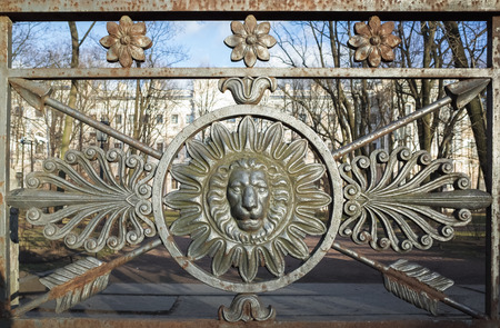Frontal view of lion head in round frame. Decoration of old metal fence in central historical part of Saint-Petersburg, Russia Standard-Bild