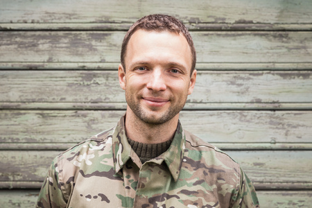 camoflauge: Young smiling Caucasian man in military camouflage uniform. Outdoor closeup portrait over green rural wooden wall Stock Photo