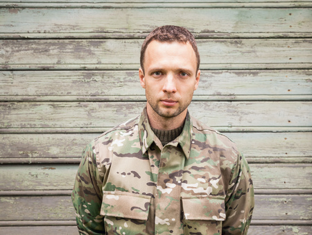 camoflauge: Young serious Caucasian man in military camouflage uniform. Outdoor closeup portrait over green rural wooden wall Stock Photo