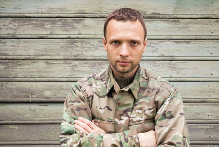 camoflauge: Young handsome Caucasian man in military camouflage uniform. Outdoor closeup portrait over green rural wooden wall Stock Photo
