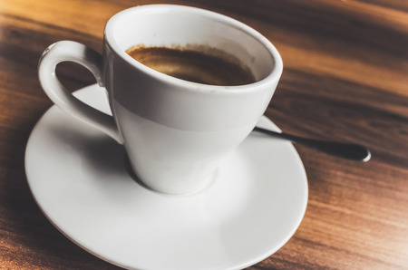 tonal: Freshly brewed espresso coffee in white cup on saucer with spoon. Closeup photo with selective focus and vintage tonal correction photo filter, old style effect