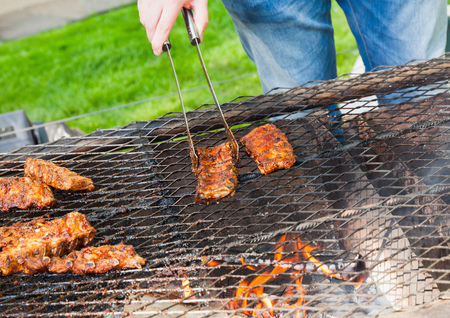 pork ribs: Man fries pork ribs with barbecue sauce on outdoor grille Stock Photo