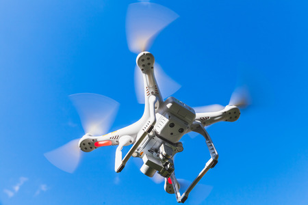 controlled: White quadrocopter flying in blue sky, drone controlled by wireless remote Stock Photo