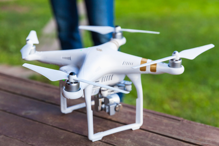 phantom: St. Petersburg, Russia - May 4, 2016: Drone quadrocopter Phantom 3 Professional with high resolution digital camera and remote control designed by the Chinese company DJI stand on a wooden floor Editorial