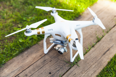 phantom: St. Petersburg, Russia - May 4, 2016: Drone quadrocopter Phantom 3 Professional with high resolution digital camera designed by the Chinese company DJI stands on a wooden floor, closeup photo