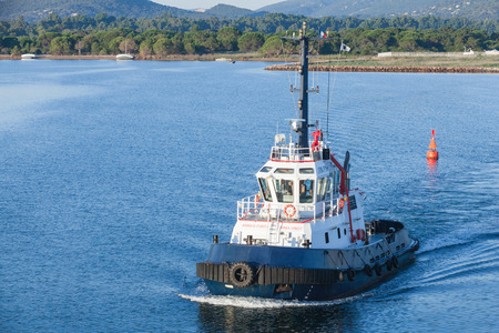 superstructure: Corsica, France - July 2, 2015: Persevero tug 40T. Industrial boat with white superstructure and dark blue hull underway on sea water