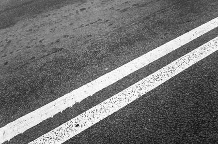 dividing: White double dividing line over black highway asphalt, closeup photo with selective focus
