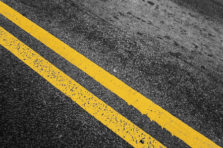 yellow line: Yellow double dividing line over black highway asphalt, closeup photo with selective focus