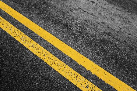 dividing: Yellow double dividing line over black highway asphalt, closeup photo with selective focus